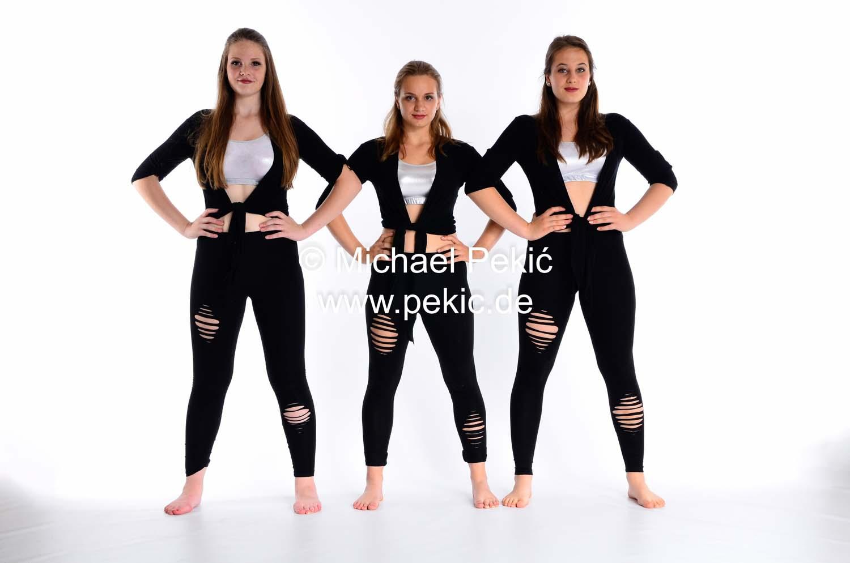 Drei junge Frauen stehen in starker Pose nebeneinander, Hände in die Hüfte, Beine auseinander