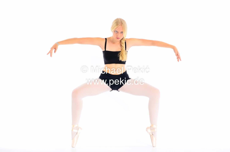 Ballerina in Hocke, steht auf Spitze, beide Arme von sich gestreckt