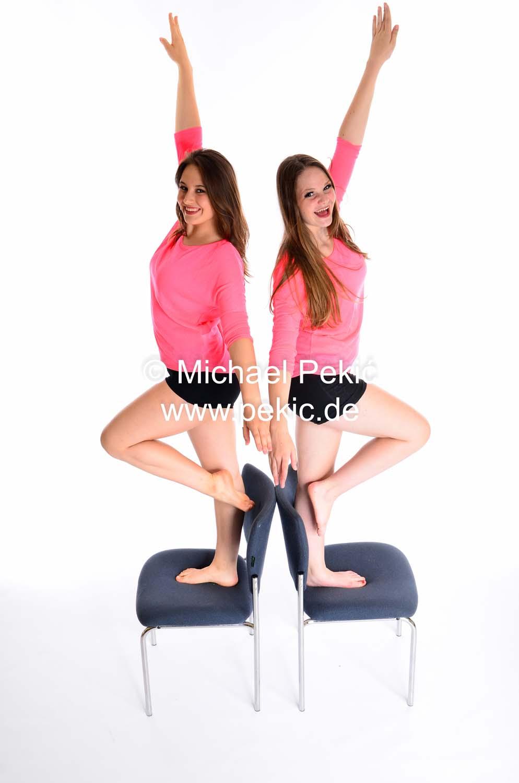 Zwei junge Frauen stehen auf Stühlen, ein Bein angewinkelt, Vogelperspektive seitlich