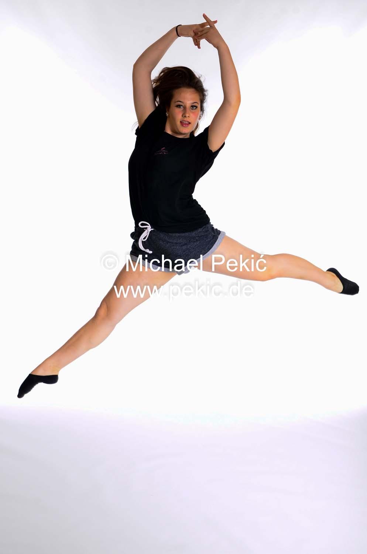 Mädchen springt in die Höhe, streckt die Arme hoch und macht einen Spagat in der Luft