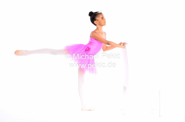 junges Mädchen nimmt Ballettpose ein, hält sich an weissem Stuhl fest