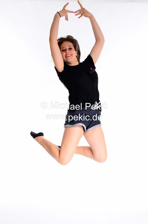 Mädchen springt in die Höhe, streckt die Arme hoch und winkelt die Beine an