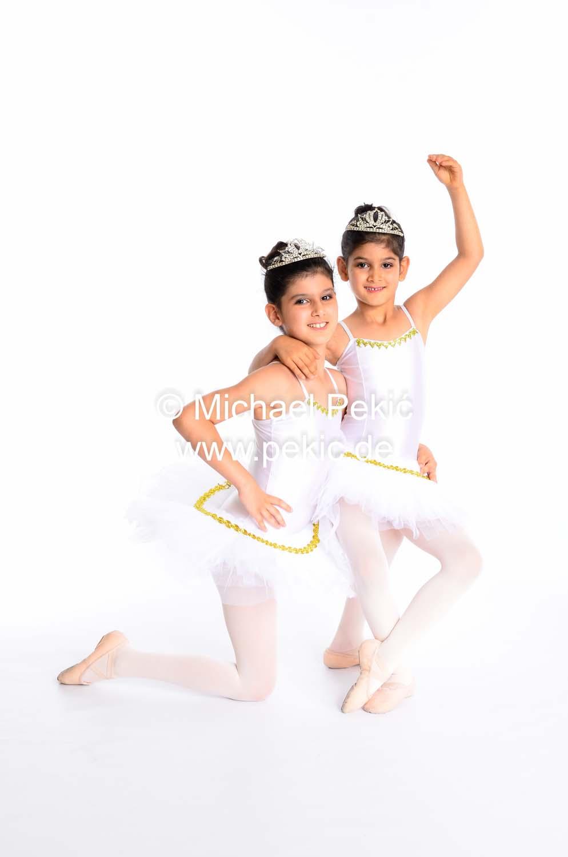 Zwei als Prinzessinnen verkleidetete Mädchen. Das jüngere Mädchen sitzt auf dem Bein des älteren Mädchens und hebt den Arm in Pose