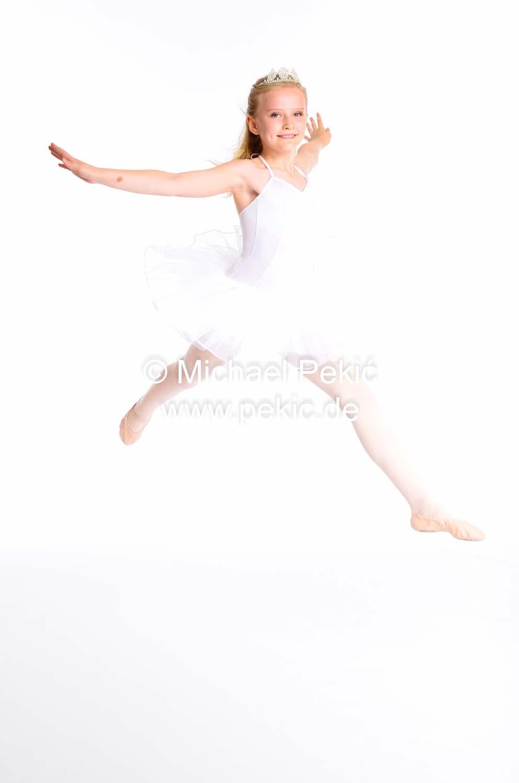 Mädchen springt voller Freude angewinkelt
