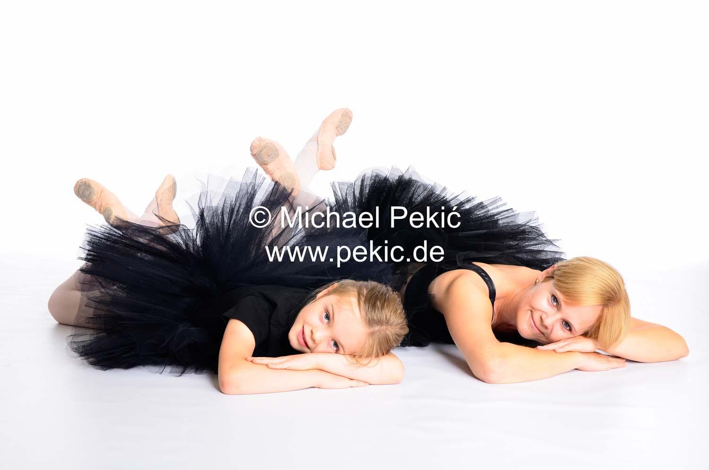 Mutter und Tochter liegend in gleicher Pose in schwarzen Kleidern den Betrachter anschauend