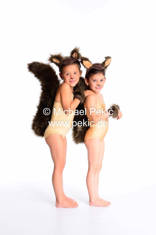 Zwei Mädchen verkleidet als Eichhörnchen, stehen hintereinander und schauen zum Betrachter