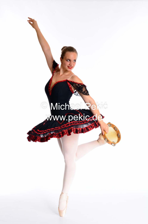 Ballerina in spanischem Look mit Tamburin in linker Hand steht auf Spitze und winkelt das rechte Bein zum Tamburin